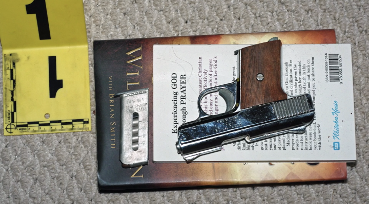 Gun at crime scene on top of religious book